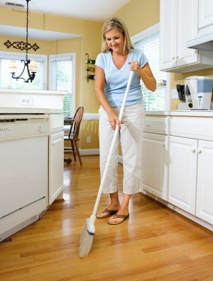 A woman sweeping a nice wood kitchen floor.