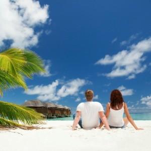 A couple sitting on the beach enjoying their honeymoon.