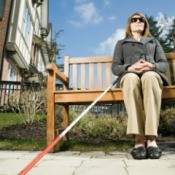 A blind woman sitting on a bench.