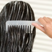A woman combing conditioner into her hair.