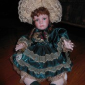 Brinn Porcelain Doll. Doll in green dress with ecru lace and lacy ruffled hat.