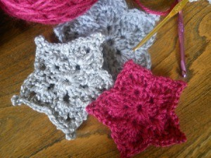 closeup of three finished stars with yarn and hooks
