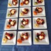 12 white plates filled with Antipasto Cups