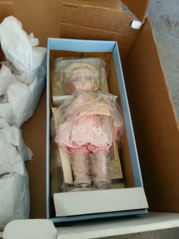 doll wrapped in plastic inside box