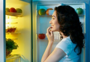 A woman looking in her refrigerator at night.