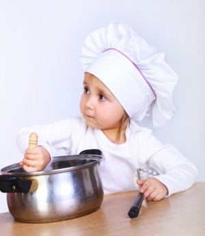 A toddler stirring food in a pot.