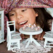 girl looking into doll house set for tea party