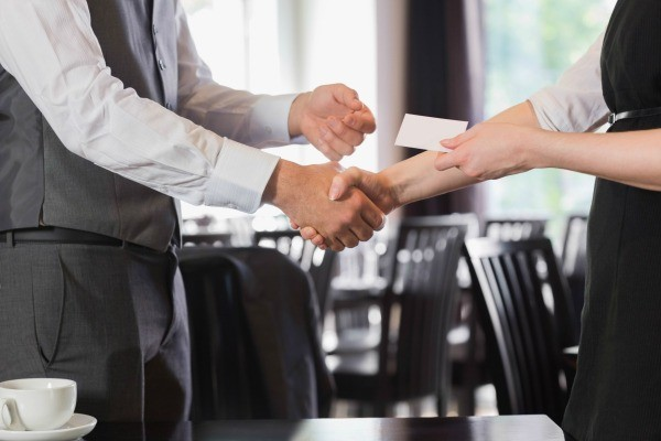 Saving money on business cards thriftyfun two people shaking hands and exchanging business cards colourmoves