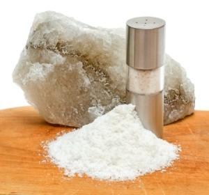 rock salt next to grinder and pile of coarsely ground salt