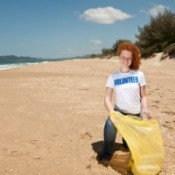 young beach cleanup volunteer on beach with yellow trash bag