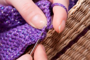 woman crocheting with purple yarn