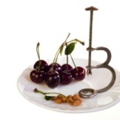 cherry pitter on plate with cherries and pits