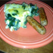 A plate with a green potato frittata and two sausages.