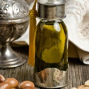 argan oil in glass container with fruits
