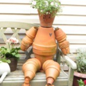 Terra cotta flowerpot man sitting on garden bench