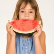 girl eating watermelon with juice dripping on blouse
