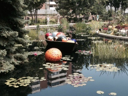 multicolored glass globes in a small wooden boat on pond with a large speckled orange ball floating nearby