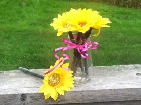 several sunflower pens in jar on railing
