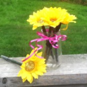 several sunflower pens in jar on railing