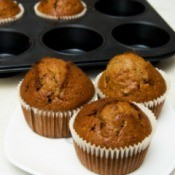 gingerbread cupcakes on plate in front of muffin pan