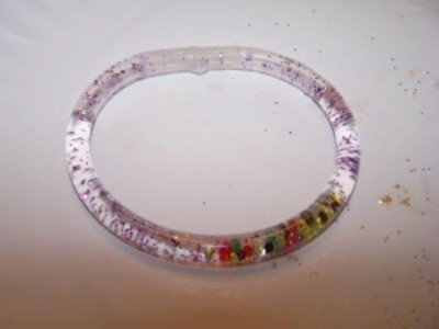 flexible tubing filled with water, glitter, and beads made into a bracelet