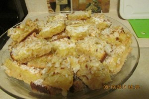 Plate piled with delicious looking lemon coconut squares.