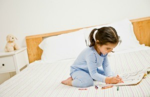 little girl in pajamas on bed coloring