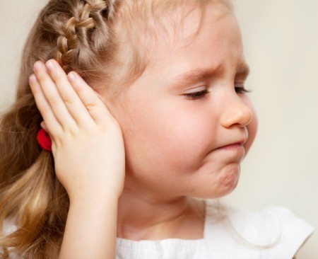 little girl frowning and holding her ear