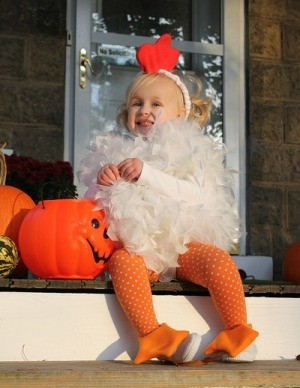 Little girl dressed as a chicken sitting on the front porch.