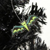 An ornament of a bat hanging on a black tree.