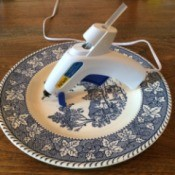 blue and white plate with glue gun resting on it
