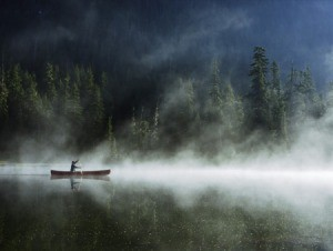 man in canoe with fog over lake