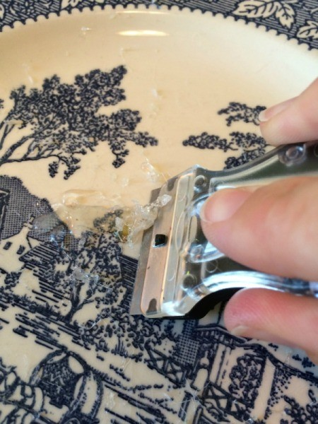 using razor blade to remove dried glue on plate
