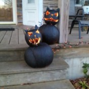 two black cat pumpkins made from a smaller carved face pumpkin on top of a larger one