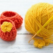 orange booties with yellow flower next to ball of yellow yarn with crochet hook