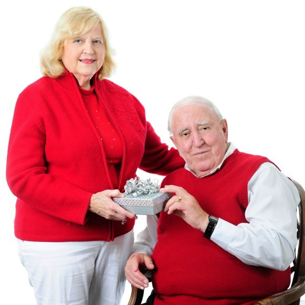 woman handing an older man a gift