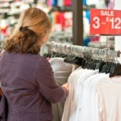 A woman looking at a clothing rack.
