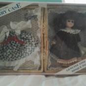 A Dandee porcelain doll in a box.