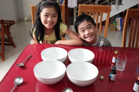 children sitting at table with supplies and bowls