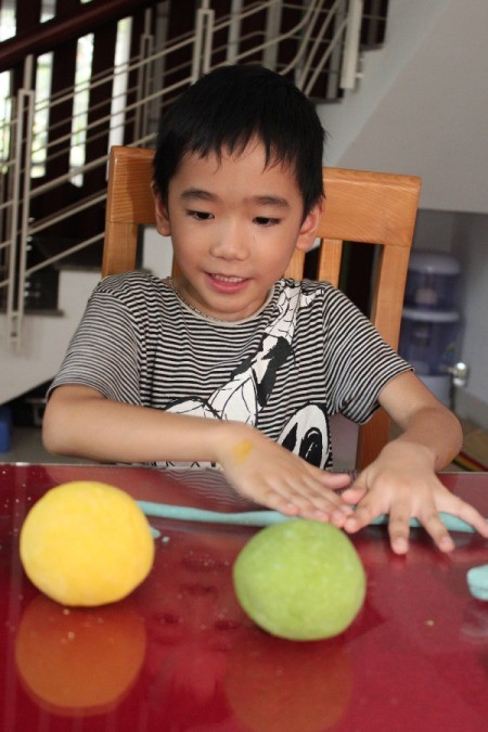 boy rolling a rope of dough