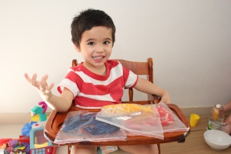 three bags of colored pasta on table in front of child