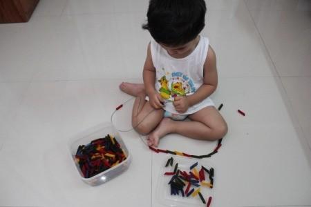 stringing colored pasta