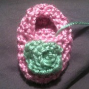 A crocheted rosebud on a baby bootie.