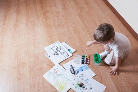 A child painting on laminate wood flooring.
