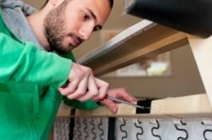 Man Repairing a Broken Couch Frame