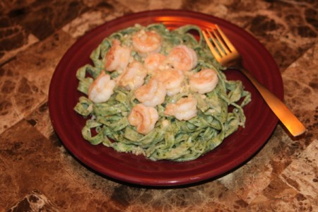 A plate of spinach pasta with shrimp.