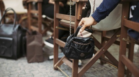 A pickpocket stealing a wallet out of a purse.