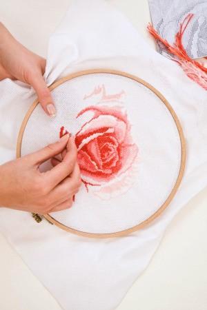 woman cross stitching a rose
