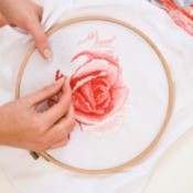 woman cross stitching a rose
