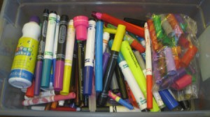 A box of markers with saved marker caps.